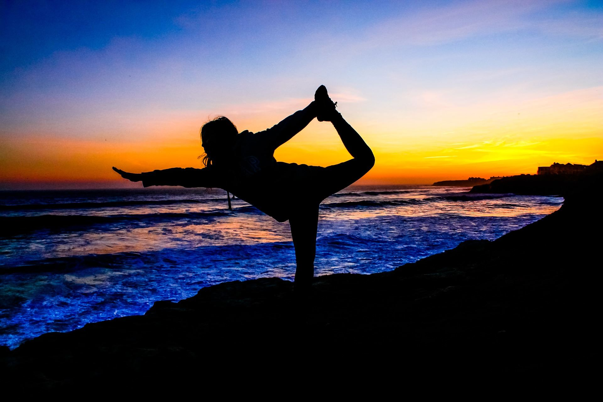 Woman, silhouetted, doing a yoga dancer pose, sunset and reflection on waves in background