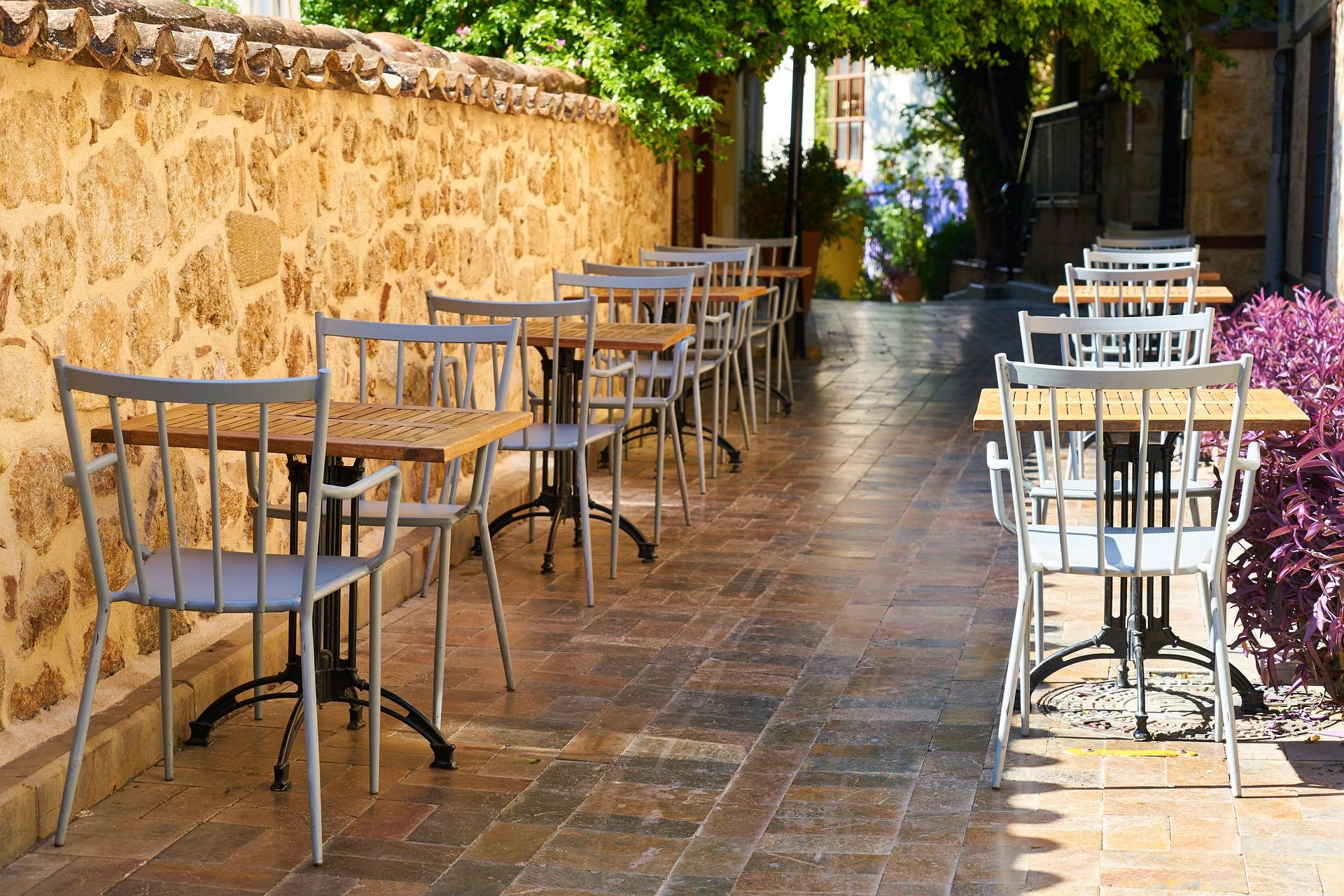 row of outdoor restaurant tables by a brick wall