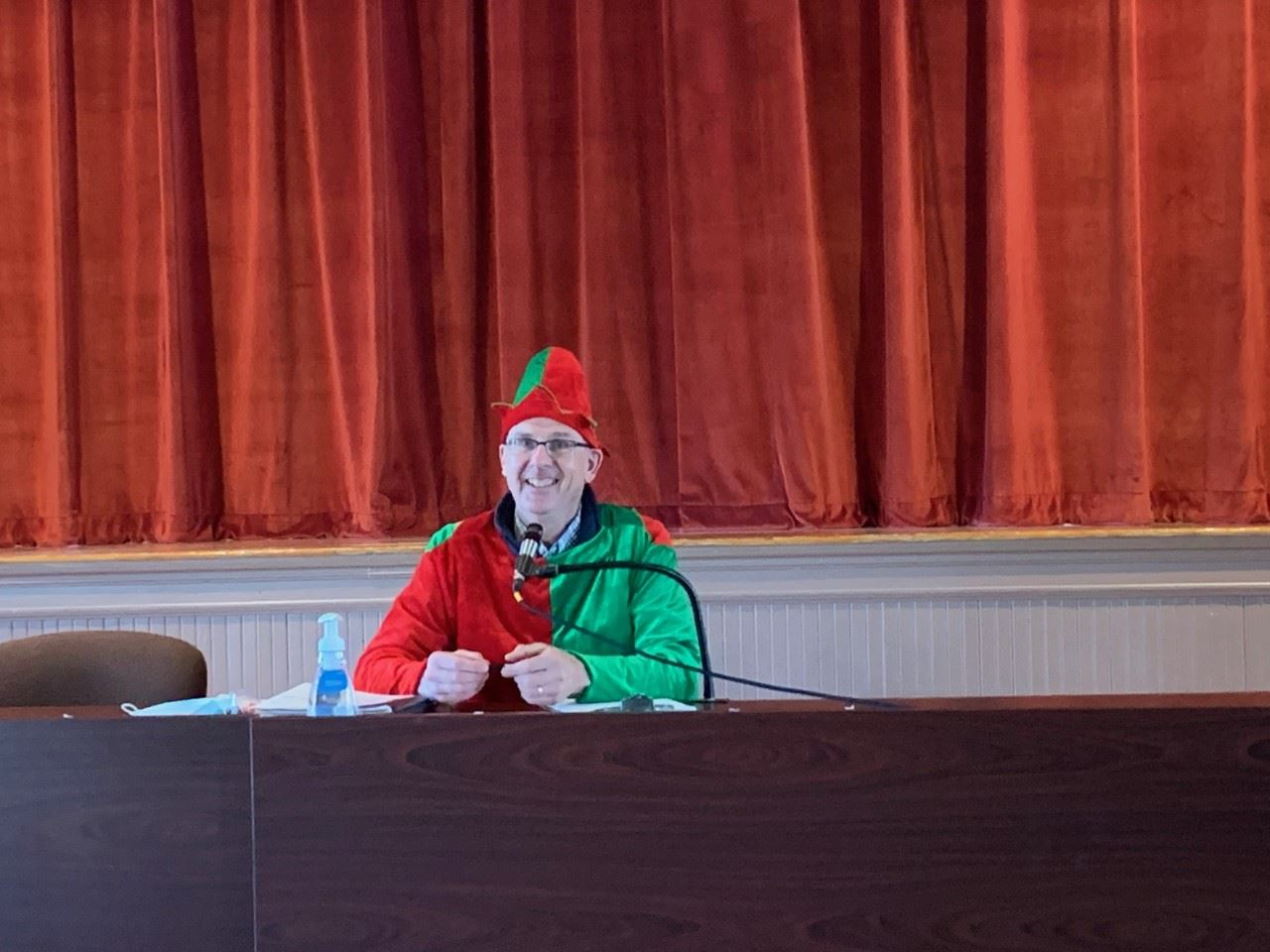 man dressed as elf addressing camera